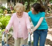 volunteer helping a senior walk